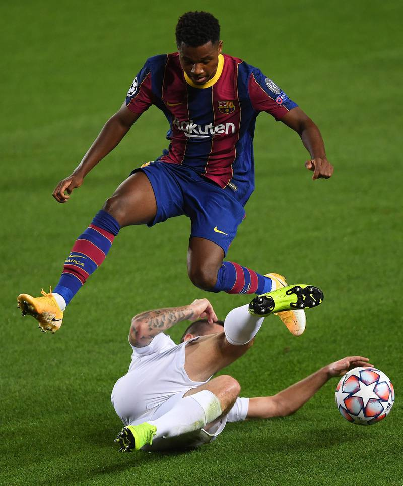 BARCELONA, SPAIN - OCTOBER 20: Ansu Fati of FC Barcelona is challenged by Endre Botka of Ferencvaros Budapest during the UEFA Champions League Group G stage match between FC Barcelona and Ferencvaros Budapest at Camp Nou on October 20, 2020 in Barcelona, Spain. Sporting stadiums around Europe remain under strict restrictions due to the Coronavirus Pandemic as Government social distancing laws prohibit fans inside venues resulting in games being played behind closed doors. (Photo by Alex Caparros/Getty Images)