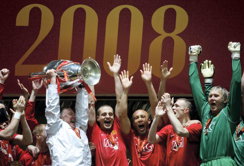 Manchester United manager Sir Alex Ferguson (L) holds up the trophy after beating Chelsea in the final of the UEFA Champions League football match at the Luzhniki stadium in Moscow on May 21, 2008. The match remained at a 1-1 draw and Manchester won on penalties after extra time.     AFP PHOTO / Adrian Dennis / AFP PHOTO / ADRIAN DENNIS
