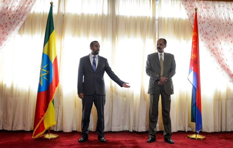 Ethiopian Prime Minister Abiy Ahmed (L) and President Isaias Afeworki of Eritrea (R) celebrate the opening of the Embassy of Eritrea in Ethiopia reopened following the official visit after twenty years, in Addis Ababa on July 13, 2018. / AFP / MICHAEL TEWELDE