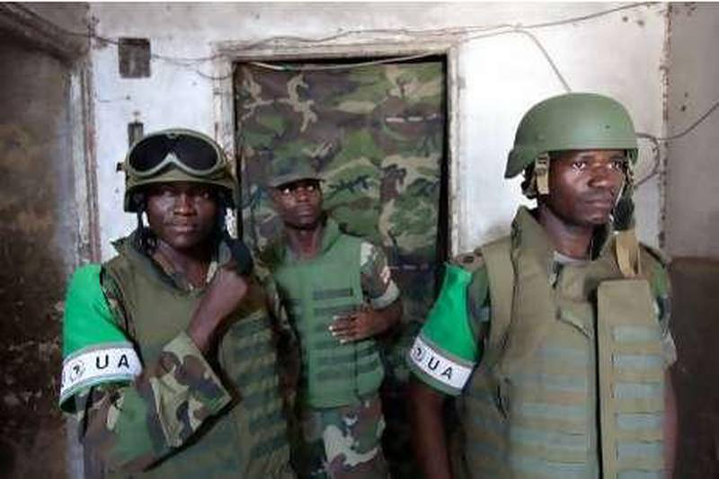 """Soldiers of the African Union Mission in Somalia (AMISOM) stand at the entrance of the strategic """"K4"""" base in Mogadishu, on November 24, 2009. Somalia's embattled president appealed to the international community on November 24, to do more to prop up his transitional government, fighting for survival against an Al Qaeda-inspired insurgency. AFP PHOTO / YASUYOSHI CHIBA"""