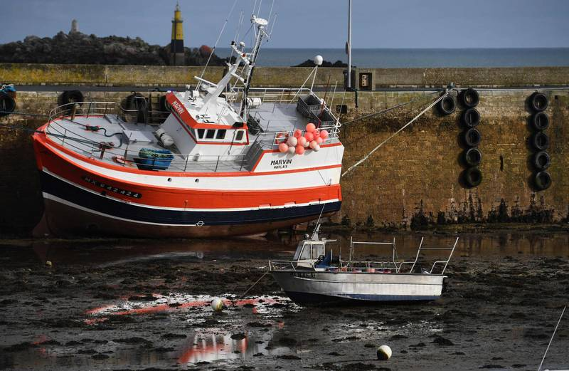 (FILES) In this file photo taken on November 13, 2020 A fishing boat sits on the sand at low tide alongside the quai in the port of Roscoff, western France.  The scramble for a post-Brexit trade deal headed into a new week on December 20, 2020 after talks were overshadowed by the coronavirus crisis and broke up with no breakthrough on fishing rights. Britain intends to assume control over its waters on January 1, but is ready to allow continued access to EU fishing fleets for a transitional period under new terms. EU fishermen fear that losing any access to the rich UK fishing waters will threaten their livelihoods.  / AFP / Fred TANNEAU