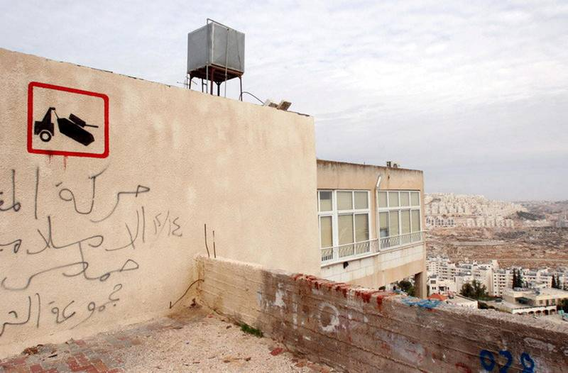 epa01191062 Illusive British graffiti artist named Banksy has painted new works in the West Bank town of Bethlehem, which might include a stencil of a tank being towed away, executed on the wall of a house on a main street in Bethlehem, on 04 December 2007. Behind is the large Jewish settlement called Har Homa, still under construction. Banksy's identity is not known and his works are not signed.  EPA/JIM HOLLANDER *** Local Caption *** 01191062