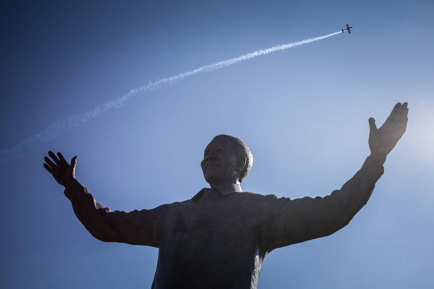 A South African airforce jet flies over a statue of Nelson Mandela at the Union Building in Pretoria during the celebrations of the 20th anniversary of Freedom day, which marks the end of the Apartheid politic, in Pretoria on April 27, 2014.    AFP PHOTO / FEDERICO SCOPPA (Photo by FEDERICO SCOPPA / AFP)