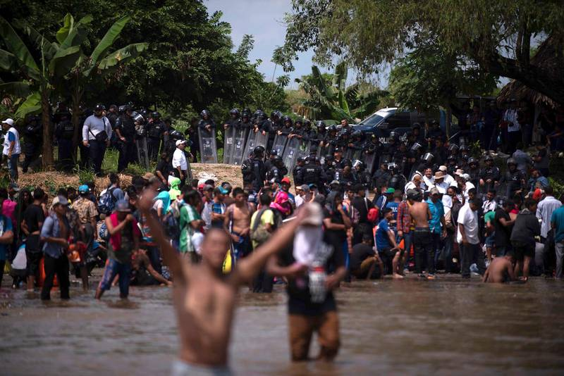 A wall of Mexican Federal Police await a new group of Central American migrants who waded in mass across the Suchiate River, that connects Guatemala and Mexico, in Tecun Uman, Guatemala, Monday, Oct. 29, 2018. The first group was able to cross the river on rafts — an option now blocked by Mexican Navy river and shore patrols. The migrants were eventually allowed passage. (AP Photo/Santiago Billy)