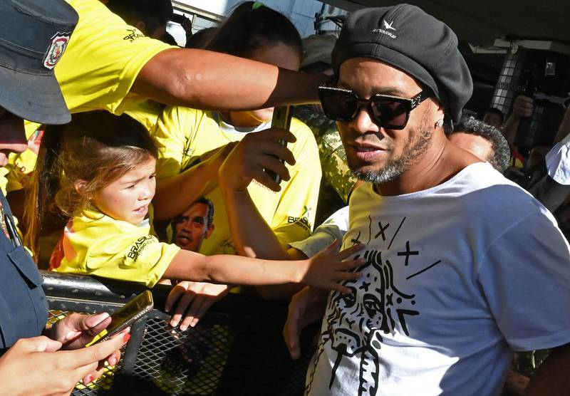 """TOPSHOT - A girl stretches to touch Brazilian ex-football star Ronaldinho Gaucho upon his arrival at Silvio Pettirossi International Airport in Luque, near Asuncion, on March 4, 2020. Ronaldinho arrived in Paraguay to present his latest book """"Genio en la Vida"""" and a health programme for girls and boys.   / AFP / Norberto DUARTE"""