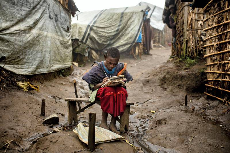 Portrait of a 12 years old girl in Katale IDP Camp in Masisi territory. She does her homework during the last daylight hours in front of her hut.