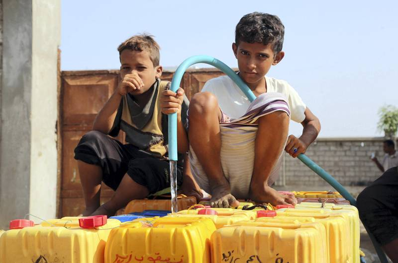 Yemeni children fill empty jerrycans with water from a donated source amid ongoing widespread disruption of water supplies in an impoverished coastal village on the outskirts of the Yemeni port city of Hodeidah, on October 18, 2016. / AFP PHOTO / STRINGER