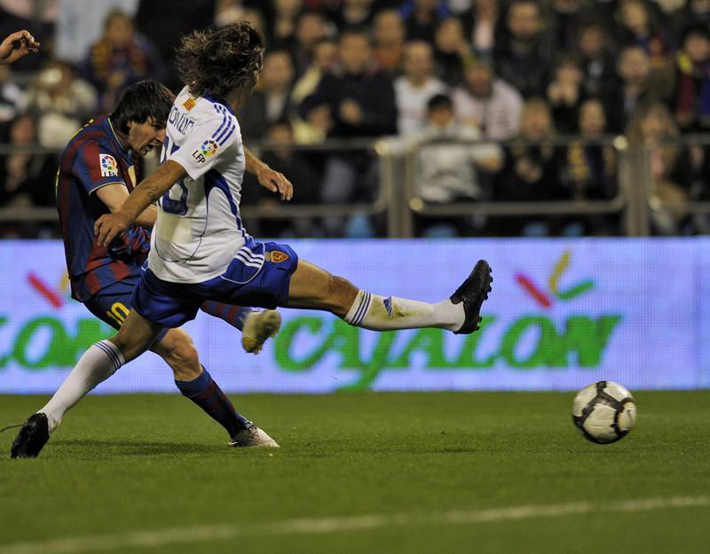 Barcelona's Argentinian forward Lionel Messi (L) kicks to score the second goal against Zaragoza during their Spanish League football match between Zaragoza and Barcelona on March 21, 2010 at La Romareda stadium in Zaragoza.   AFP PHOTO/ LLUIS GENE (Photo by LLUIS GENE / AFP)
