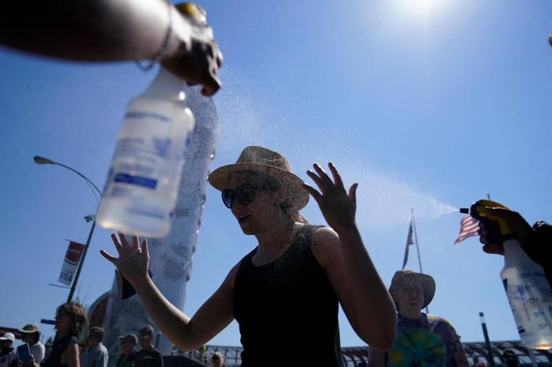 Fans gets spay with water after events were postponed due to high heat at the U.S. Olympic Track and Field Trials Sunday, June 27, 2021, in Eugene, Ore. (AP Photo/Ashley Landis)