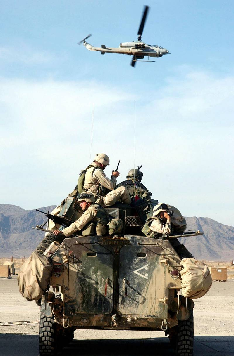 """399162 03: Marines on a Light Armored Vehicle prepare for patrol as an AH1W """"Super Cobra"""" helicopter flies by December 28, 2001 at the U.S. Marine Corps Base in Kandahar, Afghanistan. U.S. Marines are in Afghanistan in support of Operation Enduring Freedom. (Photo by Johnny Bivera/U.S. Navy/Getty Images)"""