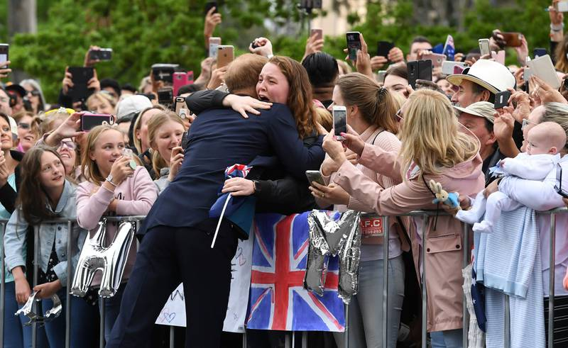 Britain's Prince Harry embraces India Brown during a public walk in Melbourne on October 18, 2018. Thousands of royal fans in Melbourne waited in the rain on October 18 to get a glimpse of Prince Harry and his pregnant wife Meghan, with some overwhelmed by the experience.  / AFP / POOL / WILLIAM WEST