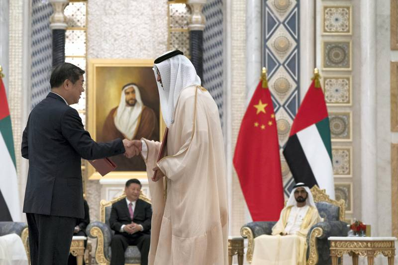 ABU DHABI, UNITED ARAB EMIRATES - July 20, 2018:  HE Dr Sultan Ahmed Al Jaber, UAE Minister of State, Chairman of Masdar and CEO of ADNOC Group (R), exchanges an MOU with a member of the Chinese delegation, at the Presidential Palace. Witnessed by HH Sheikh Mohamed bin Rashid Al Maktoum, Vice-President, Prime Minister of the UAE, Ruler of Dubai and Minister of Defence (back R) and HE Xi Jinping, President of China (back L),  ( Mohamed Al Hammadi / Crown Prince Court - Abu Dhabi ) ---
