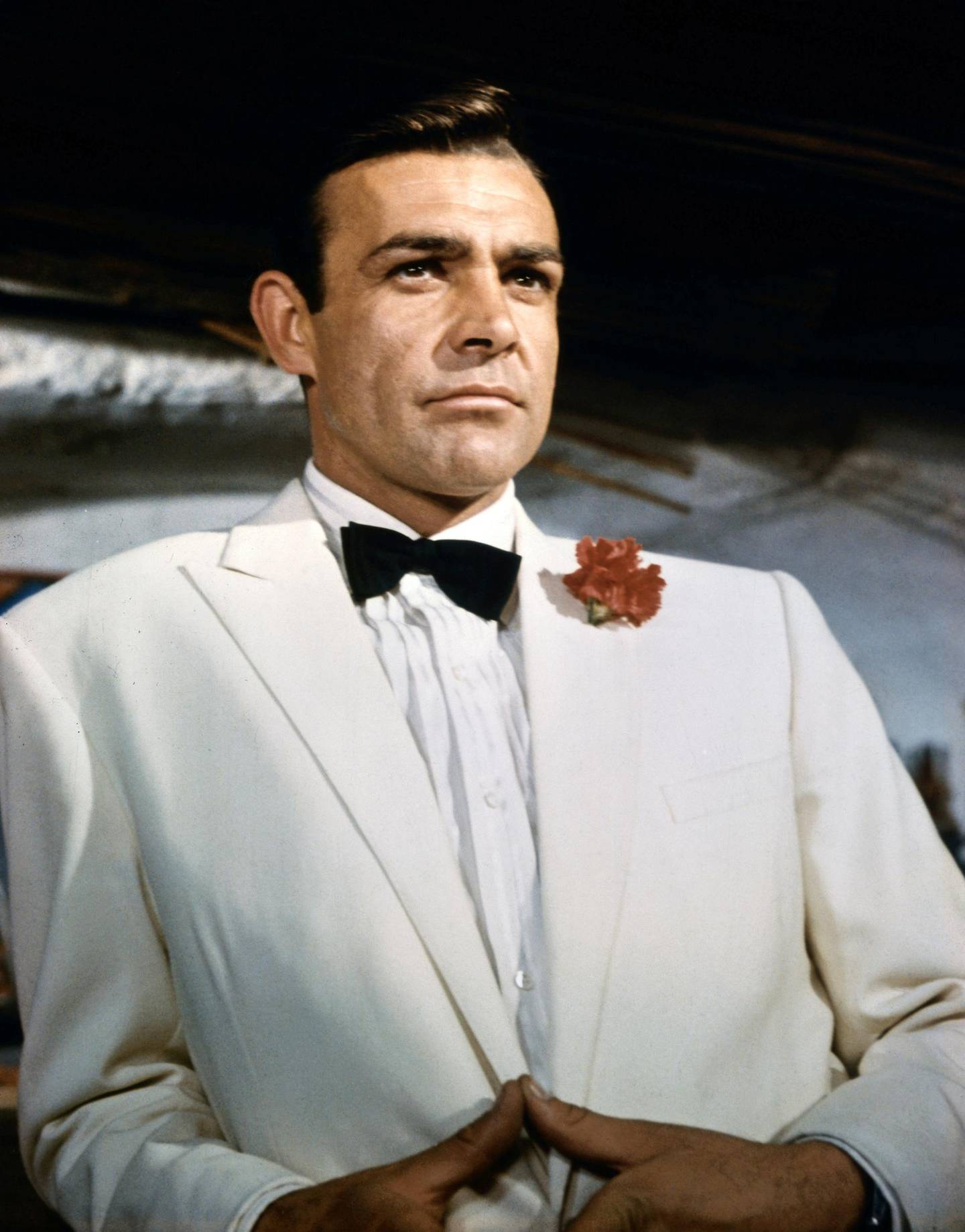 (Original Caption) ca. 1966: Waist-up portrait of Sean Connery, as James Bond, leaning against a bar and looking out across the room. Connery is wearing a white tuxedo and bow tie with a red carnation in his lapel. CONNERY; SEAN BOND; JAMES. 99/99/1966 35 U CT4X5
