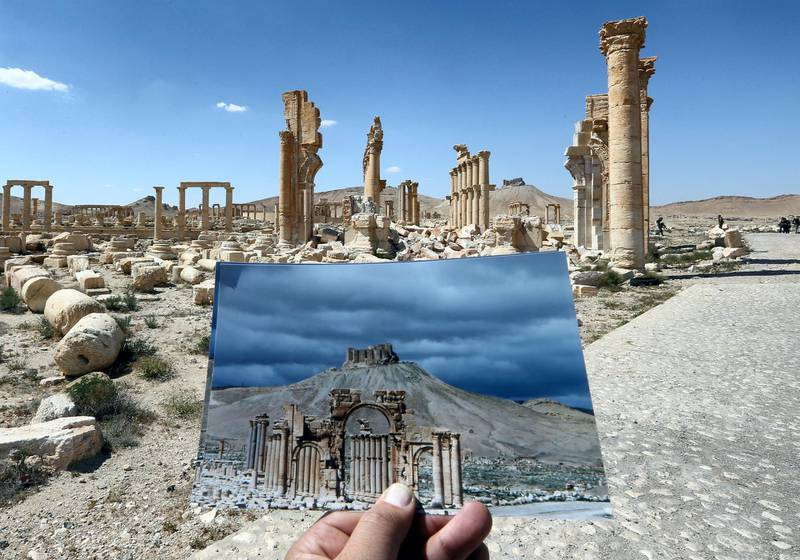 A general view taken on March 31, 2016 shows a photographer holding his picture of the Arc du Triomphe (Triumph's Arch) taken on March 14, 2014 in front of the remains of the historic monument after it was destroyed by Islamic State (IS) group jihadists in October 2015 in the ancient Syrian city of Palmyra. - Syrian troops backed by Russian forces recaptured Palmyra on March 27, 2016, after a fierce offensive to rescue the city from jihadists who view the UNESCO-listed site's magnificent ruins as idolatrous. (Photo by JOSEPH EID / AFP)
