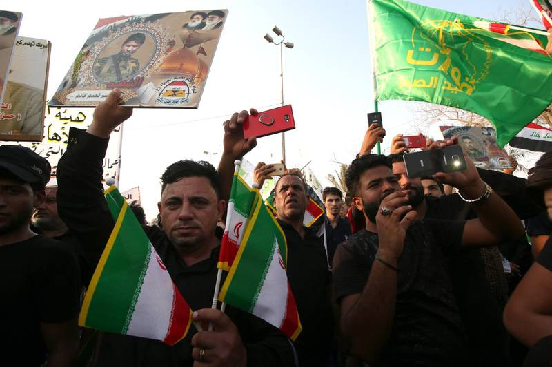 epa07023205 Supporters of Iraqi Shiite group Popular Crowd Forces carry the Iranian flag during a demonstration in Basra, southern Iraq on 15 September 2018. Dozens of Iraqis protested against the burning of the Iranian consulate and the office of Popular Crowd Forces during the protests against the government that swept Basra city last  week  EPA/HAIDER AL-ASSADEE
