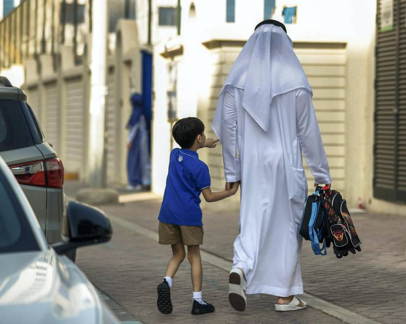 Abu Dhabi, U.A.E., September 2, 2018.  Pupils heading to school for the first day after the summer break at the Pearl Academy School on Muroor Road.-- a father walks his son to school.Contact: Victor Besa / The NationalSection:  NAReporter:  Anam Rizvi