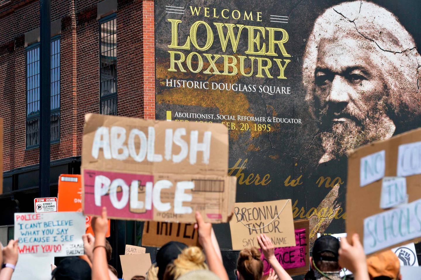 Protesters march by a photo of Frederick Douglas, a historic abolitionist, during a Juneteenth protest and march in honor of Rayshard Brooks and other victims of Police Violence in Boston, Massachusetts on June 22, 2020. / AFP / Joseph Prezioso