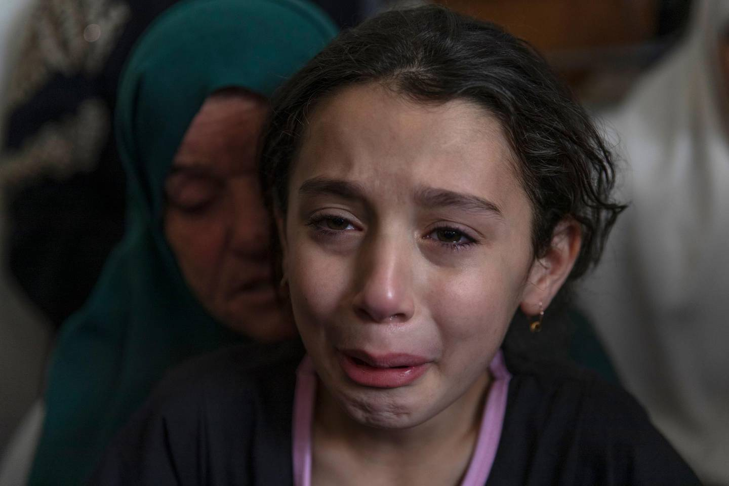 Palestinian Batoul Shamsa, 10, cries during the funeral of her brother Ahmad Shamsa, 15, in the West Bank village of Beta, near Nablus, Thursday, June. 17, 2021. The Palestinian health ministry said Thursday that Shamsa who was shot by Israeli troops in the West Bank a day earlier died of his injuries. (AP Photo/Nasser Nasser)