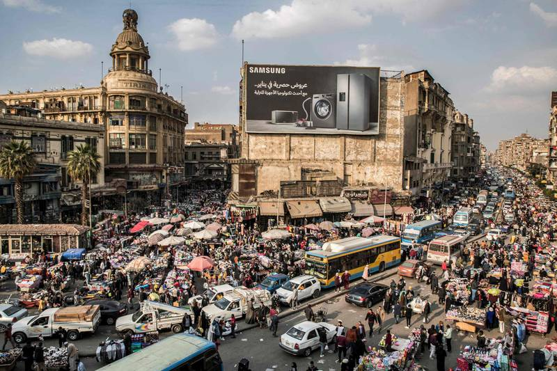 This picture taken on February 22, 2021 shows a view of vehicles stuck in a traffic jam amidst street vendors and pedlars in the central Attaba district of Egypt's capital Cairo. In gridlocked and heavily polluted Cairo, startups are searching for technological solutions to solve the transport headaches for an expanding megacity already struggling with over 20 million people. Cairo, the most populous Arab city where a fifth of all Egyptians live, is ranked 30th worst in the world for congestion, according TomTom, the Dutch vehicle navigations systems maker. / AFP / Khaled DESOUKI