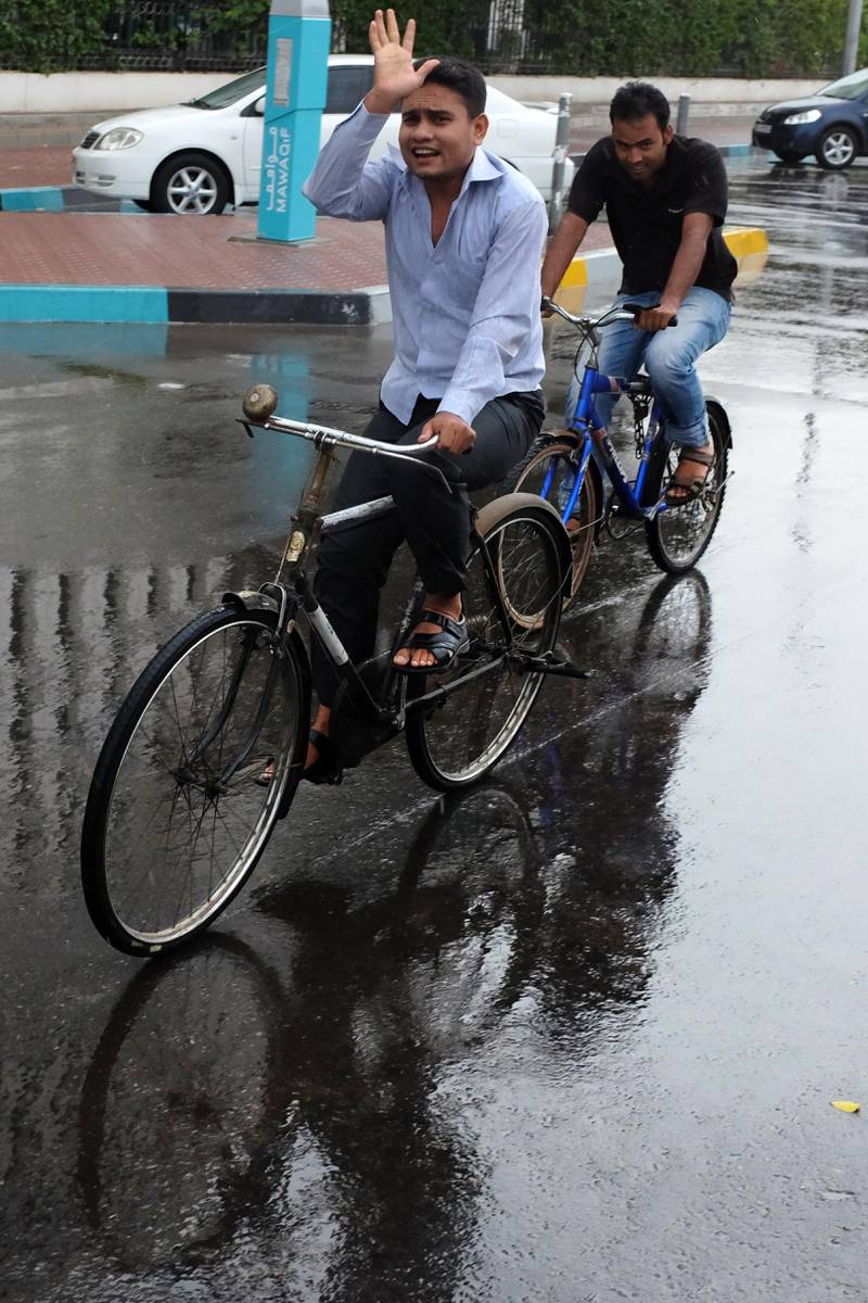 March 25th, 2013, Abu Dhabi - Two men cycle along a road as rain and high winds hit Abu Dhabi Monday afternoon. (Brian Kerrigan / The National)