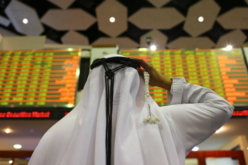 A visitor holds prayer beads while looking at financial information screens at the Dubai Financial Market (DFM) in Dubai, United Arab Emirates, on Tuesday, Nov. 10, 2015. Dubai's index declined for three straight months after a collapse in the price of crude battered economies in the oil-producing nations of the Gulf Cooperation Council. Photographer: Jasper Juinen/Bloomberg