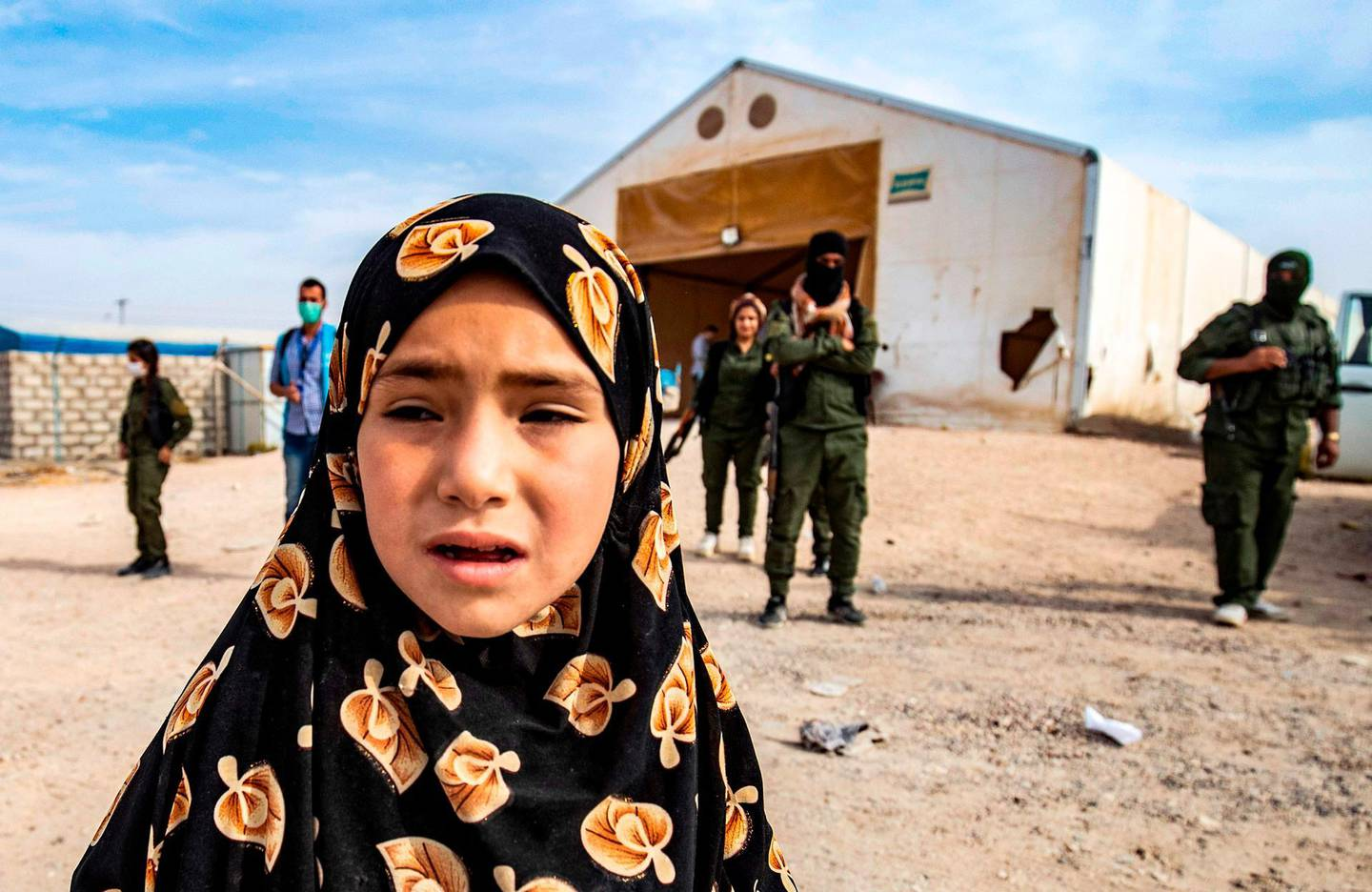 Kurdish fighter stand guard as Syrian child, suspected of being related to Islamic State (IS) group fighters, waits at the Kurdish-run al-Hol camp, before being released along with women and children to return to their homes, in the al-Hasakeh governorate in northeastern Syria, on October 28, 2020.   / AFP / Delil SOULEIMAN