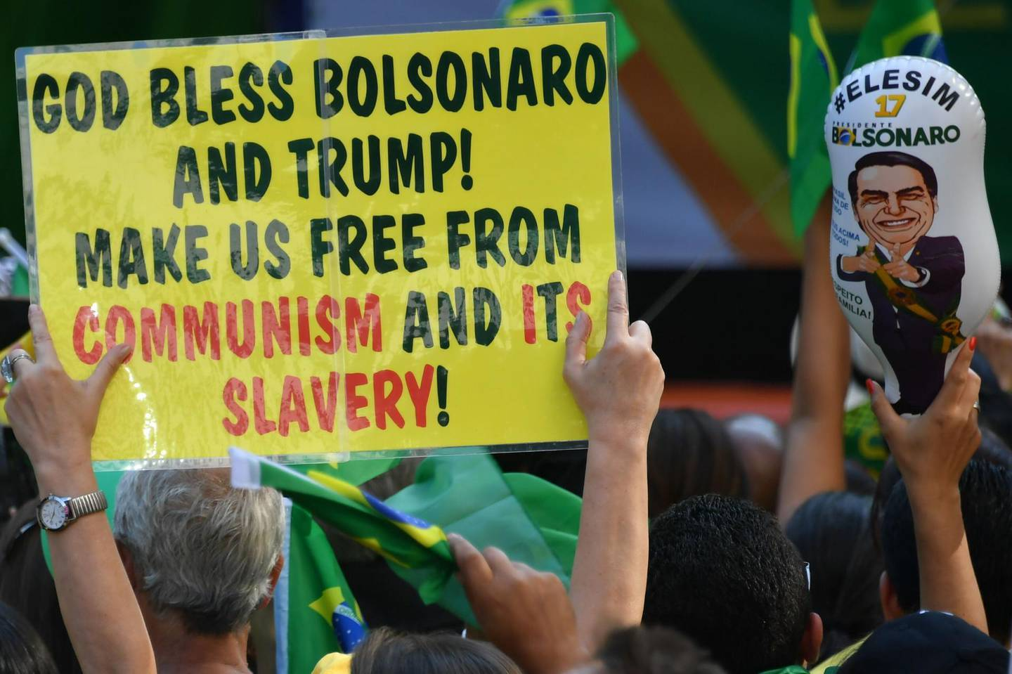 Supporters of Brazilian right-wing presidential candidate Jair Bolsonaro take part in a rally along Paulista Avenue in Sao Paulo Brazil on October 21 2018. Barring any last-minute upset, Brazil appears poised to elect Jair Bolsonaro, a populist far-right veteran politician, as its next president in a week's time. / AFP / NELSON ALMEIDA