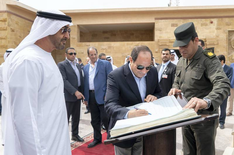 AL ALAMEIN, EGYPT - March 28, 2019: HE Abdel Fattah El Sisi President of Egyp (C) signs the guests book during a tour at Al Alamein Military Museum. Seen with HH Sheikh Mohamed bin Zayed Al Nahyan, Crown Prince of Abu Dhabi and Deputy Supreme Commander of the UAE Armed Forces (L).  ( Rashed Al Mansoori / Ministry of Presidential Affairs ) ---