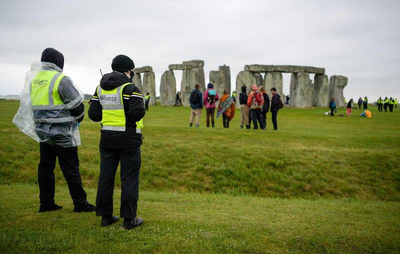 AMESBURY, ENGLAND - JUNE 21: Security guards look on after a large number of people enter the closed site at Stonehenge on June 21, 2021, in Amesbury, United Kingdom. English Heritage, which manages the site, said, 'With this week's news that the Government is delaying the lifting of the remaining Covid-19 restrictions on 21 June we have taken the difficult decision to cancel the planned Summer Solstice celebrations at Stonehenge this year'. (Photo by Finnbarr Webster/Getty Images)