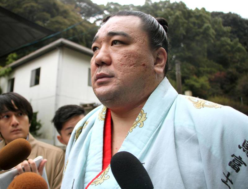 Mongolian sumo grand champion Harumafuji speaks to journalists after morning training for the ongoing Kyushu Grand Sumo Tournament in Dazaifu, southwestern Japan, Tuesday, Nov. 14, 2017. Japanese sumo officials are investigating allegations that Harumafuji hit his fellow Mongolian wrestler Takanoiwa in the head with a beer bottle at a party in October, fracturing his skull base and causing other injuries. (Kyodo News via AP)