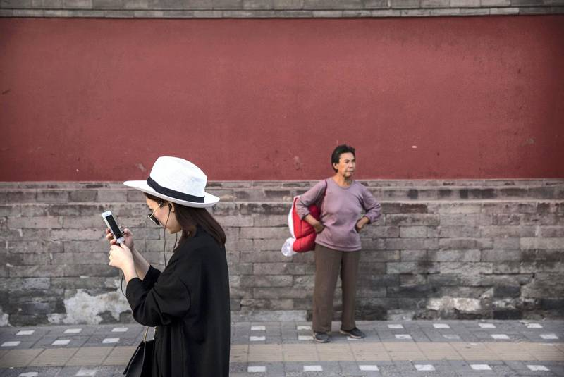 BEIJING, CHINA - SEPTEMBER 18:  A Chinese woman uses her smartphone as she walks near the Drum Tower on September 18, 2014 in central Beijing, China. Many of the traditonal homes in the Chinese capital have been demolished, making way for large high rise projects.  (Photo by Kevin Frayer/Getty Images)