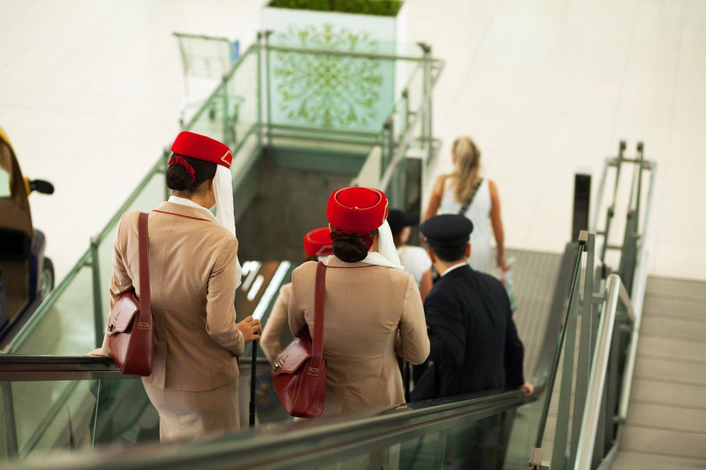 Bangkok, Thailand - July 1, 2016: Rearshot of stewardesses of Emirates airline on escalator in airport Bangkok Survanabhumi. Crew member are on way down in hall to gates.
