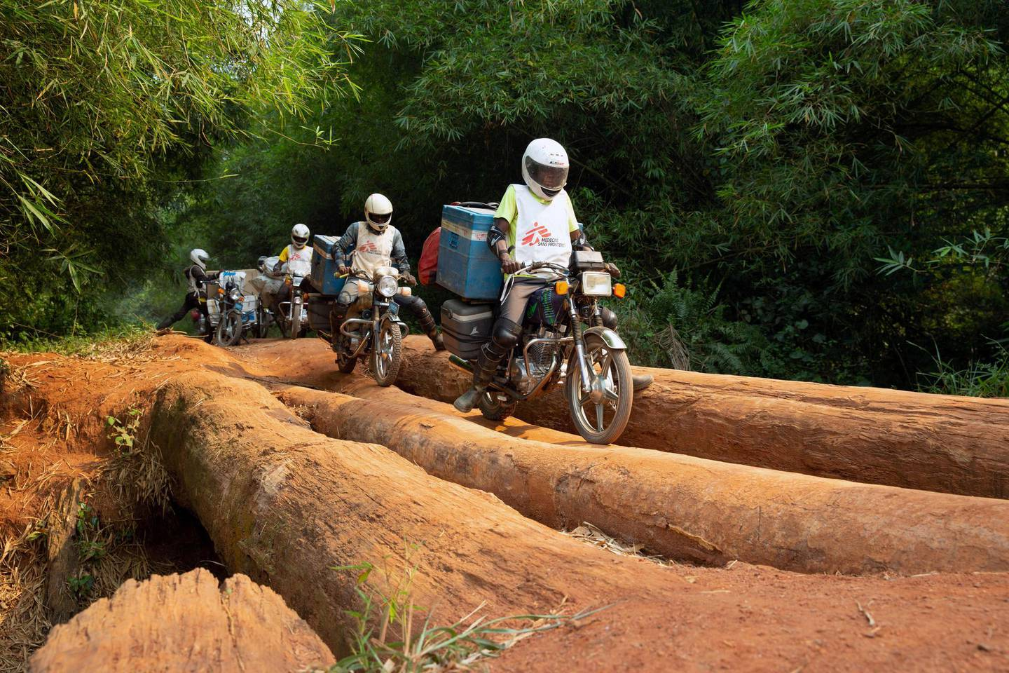 FILE PHOTO: A motorcycle convoy carrying vials of measles vaccine and other supplies for medial NGO Doctors Without Borders (MSF) crosses a log bridge on a road between Lisala and Boso-Manzi in Mongala province in the Democratic Republic of Congo February 27, 2020. Picture taken February 27, 2020. REUTERS/Hereward Holland/File Photo