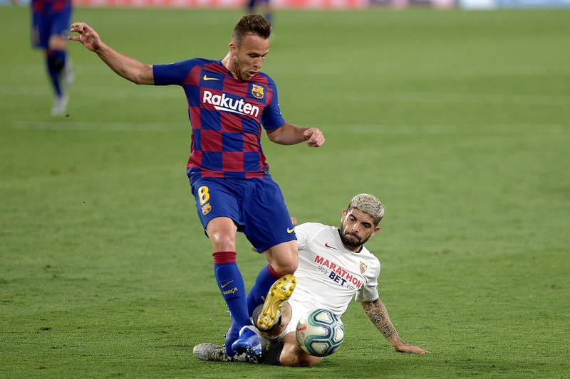 Sevilla's Argentinian midfielder Ever Banega (R) challenges Barcelona's Brazilian midfielder Arthur (L) during the Spanish league football match between Sevilla FC and FC Barcelona at the Ramon Sanchez Pizjuan stadium in Seville on June 19, 2020. (Photo by CRISTINA QUICLER / AFP)