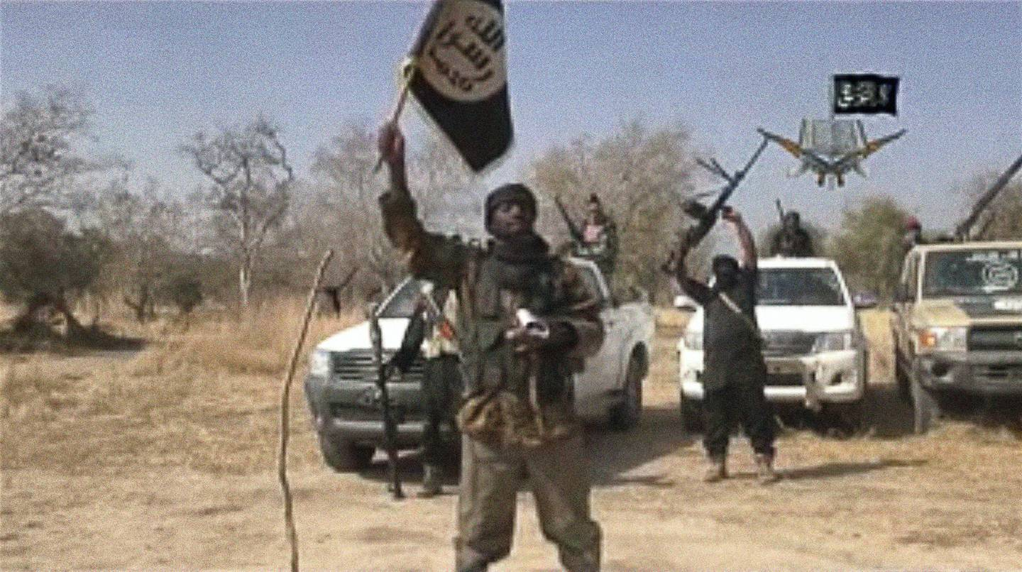 """A screen grab made on January 20, 2015 from a video of Nigerian Islamist extremist group Boko Haram obtained by AFP shows the leader of the Islamist extremist group Boko Haram Abubakar Shekau holding up a flag as he delivers a message. Boko Haram has claimed a massive attack feared to be the worst in its six-year insurgency and threatened Nigeria's neighbours, as talks began for a regional response to the militants and fears grew of further violence. """"We killed the people of Baga. We indeed killed them, as our Lord instructed us in His Book,"""" Shekau said in the 35-minute message, which was posted on YouTube. AFP PHOTO / BOKO HARAM  -- RESTRICTED TO EDITORIAL USE - MANDATORY CREDIT """"AFP PHOTO / BOKO HARAM"""" - NO MARKETING NO ADVERTISING CAMPAIGNS - DISTRIBUTED AS A SERVICE TO CLIENTS -- (Photo by - / BOKO HARAM / AFP)"""