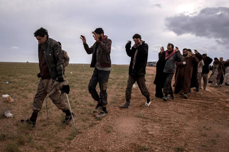Men suspected of belonging to ISIS walk to be screened by Syrian Democratic Forces outside Baghouz, Syria 28 February 2019. Campbell MacDiarmid