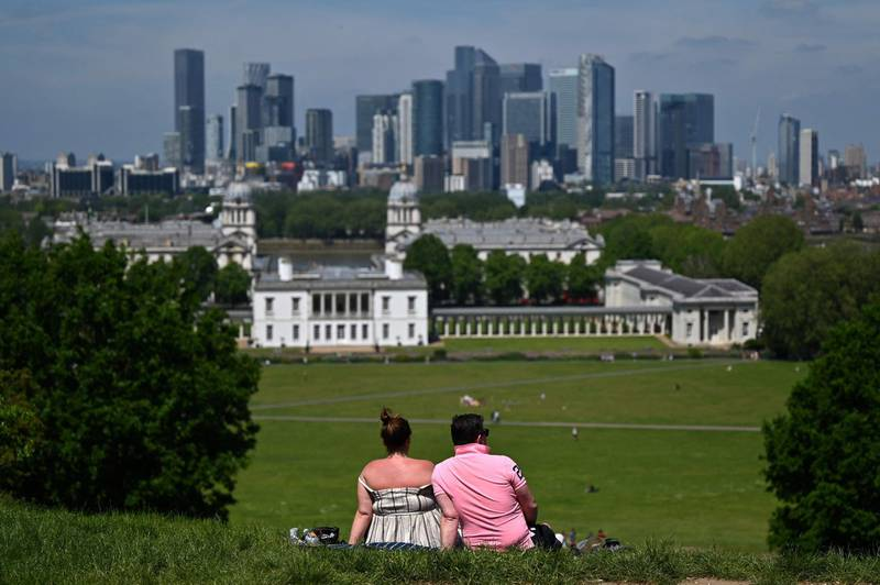 People look at the City of London skyline as they enjoy the warm weather in Greenwich Park, south east London on June 3, 2021. Much of Britain has enjoyed several days of fine weather with top temperatures reaching above 25 degrees Celsius. / AFP / JUSTIN TALLIS