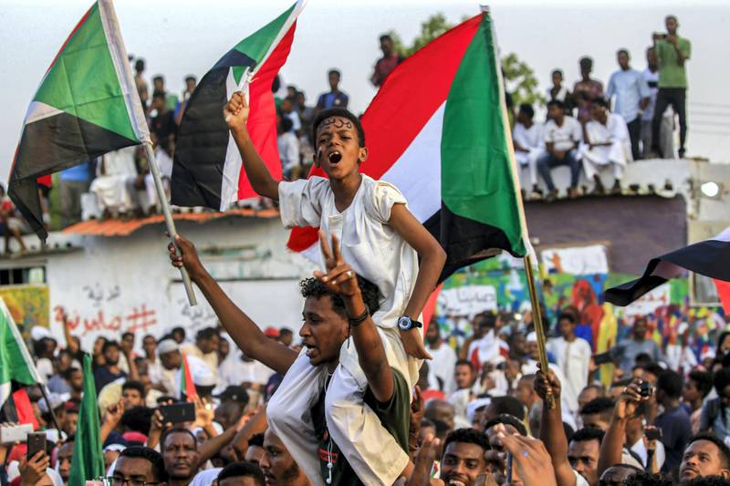 """A Sudanese boy wearing facepaint on his forehead reading in Arabic """"civilian"""" chants slogans while seated on the shoulders of a man as people celebrate after protest leaders struck a deal with the ruling generals on a new governing body, in the capital Khartoum's eastern district of Burri on July 5, 2019, - The deal, reached in the early hours of July 5 after two days of hard-won talks brokered by Ethiopian and African Union mediators, provides for the interim governing body to have a rotating presidency, as a compromise between the positions of the generals and the protesters. The blueprint proposes that a general hold the presidency for the first 18 months of a three-year transition, with a civilian taking over for the rest. (Photo by ASHRAF SHAZLY / AFP)"""