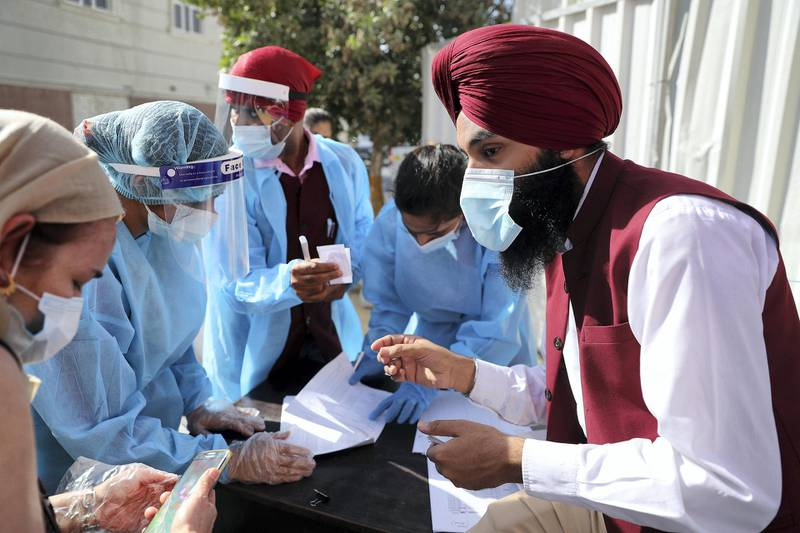 DUBAI, UNITED ARAB EMIRATES , Feb 6 – HEALTH WORKERS WITH THE LIST OF PEOPLE WHO ARE GETING THE FIRST DOSE OF SINOPHARM VACCINATION DURING THE VACCINATION DRIVE AT THE GURU NANAK DARBAR GURUDWARA IN DUBAI. Guru Nanak Darbar Gurudwara has partnered with Tamouh Health Care LLC, to provide on-site Sinopharm Vaccination for all residents of the UAE free of charge on 6th, 7th & 8th February 2021. (Pawan Singh / The National) For News/Online