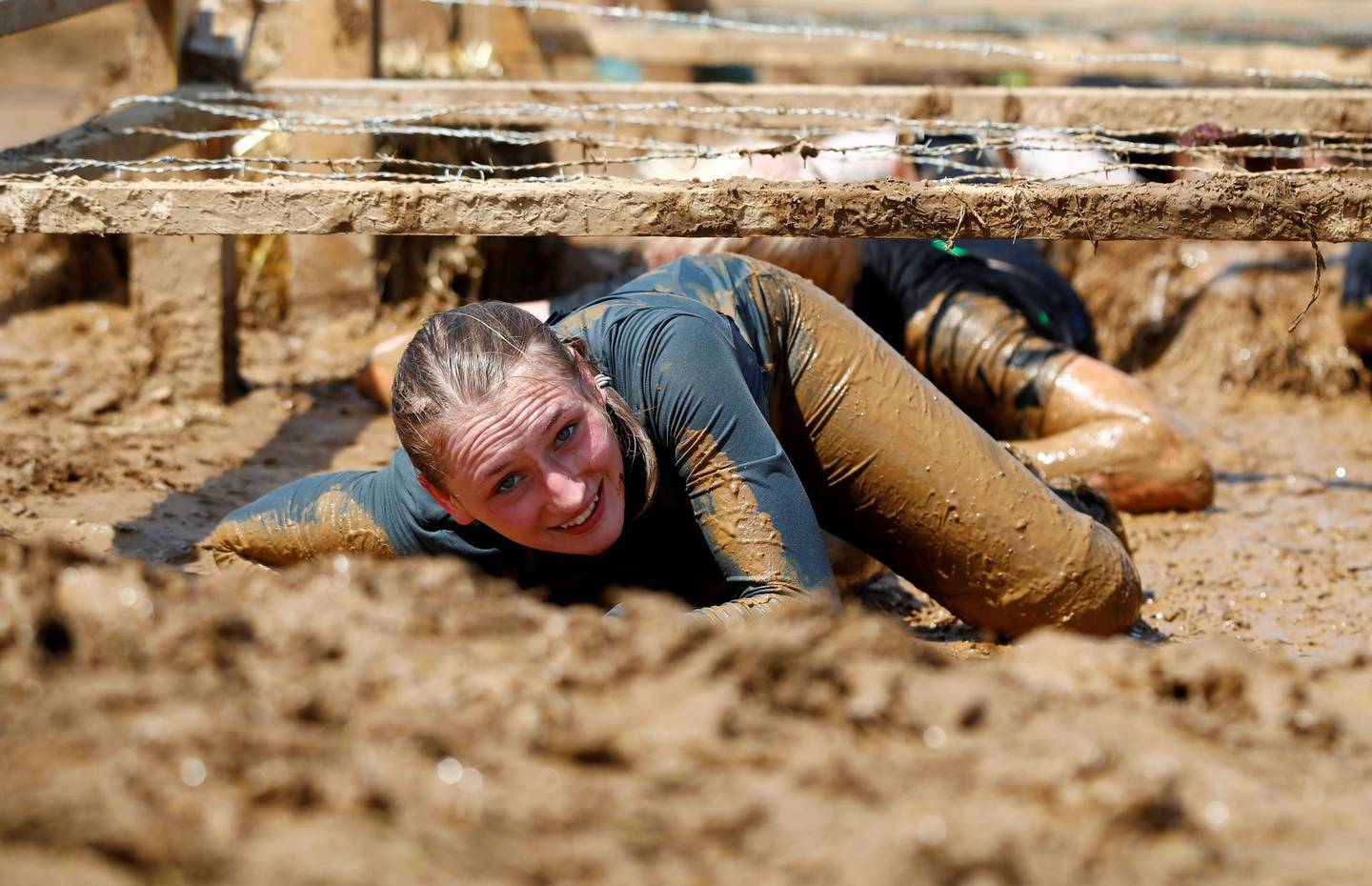 """FILE PHOTO: A woman crawls through an obstacle called """"kiss of mud"""" during the Tough Mudder untimed hardcore endurance event in Arnsberg, Germany June 1, 2019.  REUTERS/Wolfgang Rattay/File Photo"""