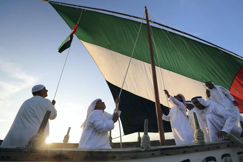 Fujairah, United Arab Emirates - November 04, 2019: Emirati fisherman hoist the UAE flag on their boat in Dibba. Monday the 4th of November 2019. Fujairah. Chris Whiteoak / The National