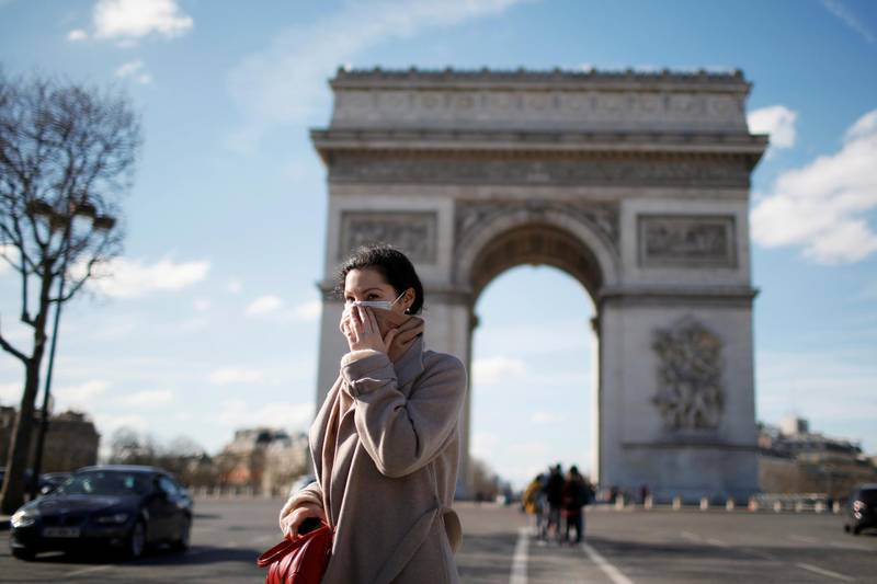 A woman wearing a protective mask, walks near Arc de Triomphe following France's Prime Minister announcement to close most all non-indispensable locations, cafes, restaurants, cinemas, nightclubs and shops as France grapples with an outbreak of coronavirus (COVID-19) disease, in Paris, France, March 15, 2020. REUTERS/Gonzalo Fuentes     TPX IMAGES OF THE DAY