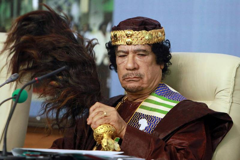 FILE - In this Sept. 8 2010 file photo, Libyan leader Moammar Gadhafi fans his face during the Forum of Kings, Princes, Sultans, Sheikhs and Mayors of Africa in Tripoli. President Trump and his hawkish national security adviser have both referenced the Libya model ahead of the much-vaunted summit with North Korea's Kim Jun Un, but what is the context?(AP Photo/Abdel Magid Al Fergany, file)