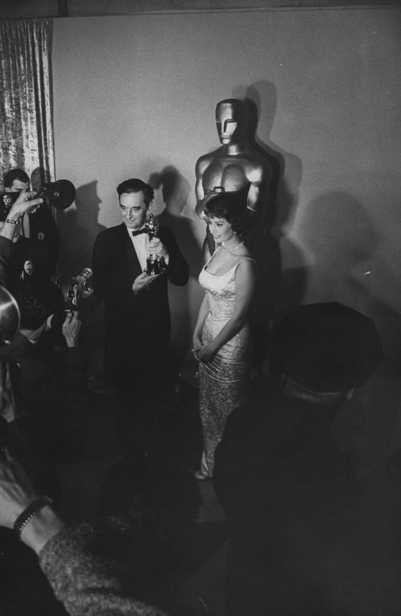 Movie director David Lean (L) stands holding the Oscar actress Sophia Loren (R) presented to him at the Academy Awards.  (Photo by Ralph Crane/The LIFE Picture Collection via Getty Images)