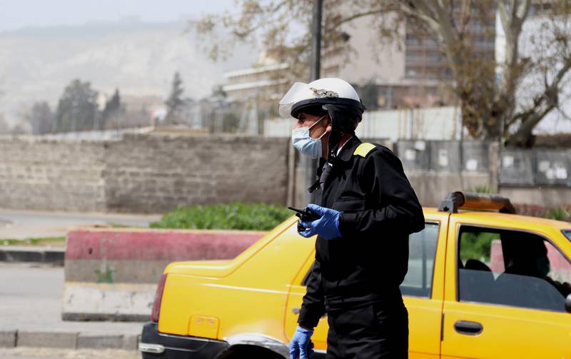 epa08319353 A policeman wearing face mask walks in Damascus, Syria, 24 March 2020. Syrian government introduced measures to prevent the spread of the coronavirus after Syria announced the first case of covid19 on 21 March. Syria imposed a curfew from 6pm to 6am local time as of 24 March, suspended work in the ministries and its affiliated entities until further notice and closed markets and suspend all commercial, service, cultural and social activities.  EPA/YOUSSEF BADAWI