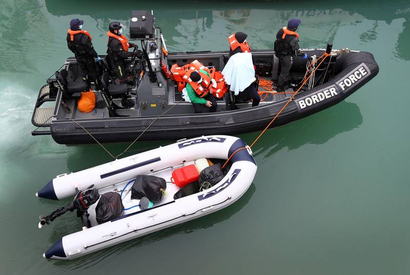 A group of people thought to be migrants are brought into port by Border Force officers following a small boat incident in the Channel, at Dover southern England, Monday March 8, 2021. (Gareth Fuller/PA via AP)