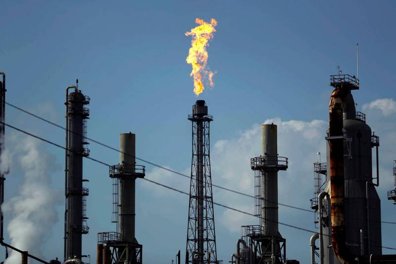 FILE - In this Thursday, Aug. 31, 2017, file photo, a flame burns at the Shell Deer Park oil refinery in Deer Park, Texas. The price of crude oil barely moved in 2017, and energy companies faded after a big gain the year before. (AP Photo/Gregory Bull, File)