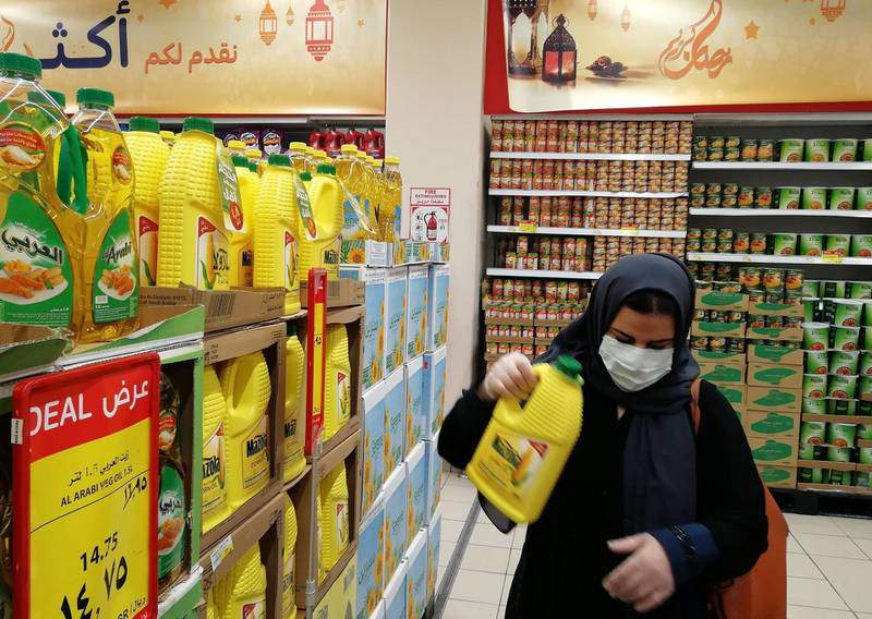 A picture taken on March 25, 2020 shows a veiled woman wearing a protective mask as she shops at a supermarket in the Saudi capital Riyadh. Saudi Arabia has reported 767 coronavirus infections -- the highest in the Gulf -- and faces the double blow of virus-led shutdowns and crashing oil prices. / AFP / FAYEZ NURELDINE