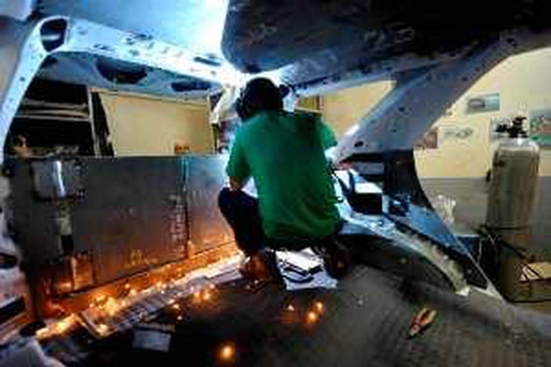 A worker welds metal plate at the rear of the Sport Utility Vehicle at Exo Armoring in Cainta Rizal suburban Manila on January 6, 2010. Exo Armoring manufactures average of 40 bulletproof cars a year.  THENATIONAL PHOTO / JAY DIRECTO *** Local Caption ***  JAY06-PHILIPPIN-3533.jpg