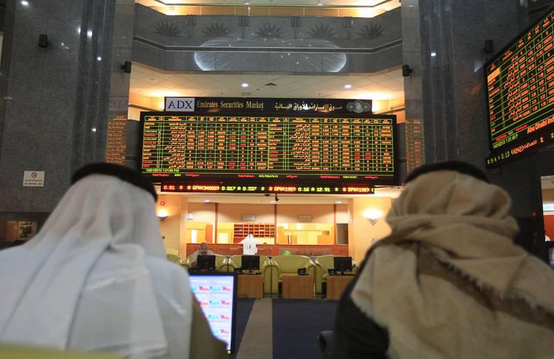 ABU DHABI - UNITED ARAB EMIRATES - 14JAN2013 - Share holders watch the display of share market at (ADX) Abu Dhabi Securities Exchange. Ravindranath K / The National